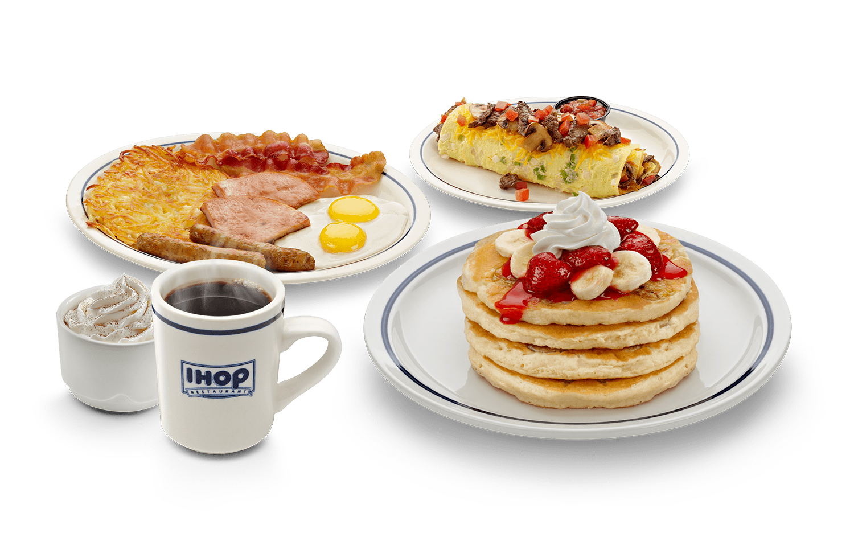 Pratos de café da manhã do fast food nos estados unidos chamado ihop. Tem panquecas, waffle com creme e ovos com bacon, além da xícara de café.