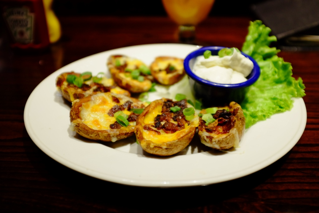 Batatas cortadas ao meio e assadas com queijo, bacon e cebolinha. O creme é sour cream.
