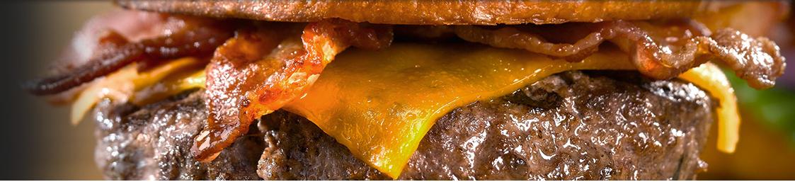 Fast Food Estados Unidos - Apenas o recheio do hamburguer da Uno pizzeria e grill com bacon e tomate saindo do pão.
