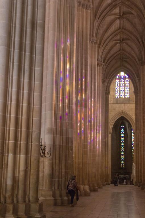 Interior da igreja de Batalha coloridamente iluminado pelo sol que bate nos vitrais