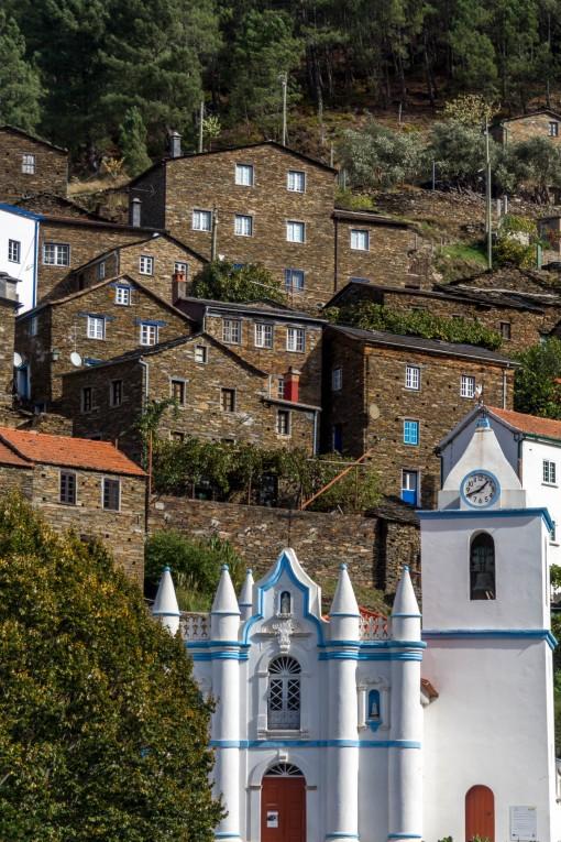 A igrejinha branca se destaca das casas de xisto ao fundo