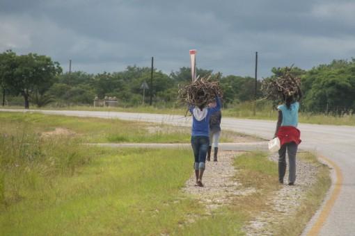 No meio de uma estrada, longe de tudo, encontramos essas garotas carregando gravetos.