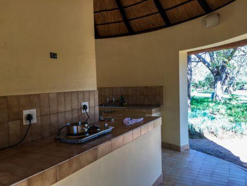 Cozinha coletiva aberta com fogão e pia.