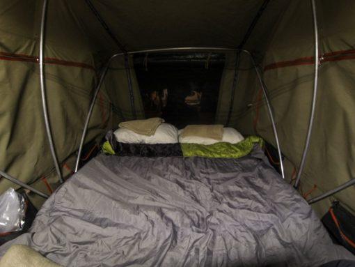 Barraca de teto armada e arrumada com travesseiros e saco de dormir