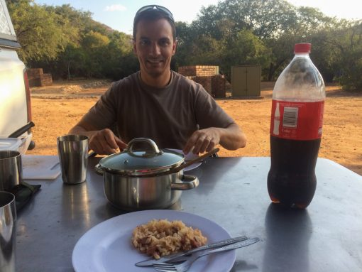 Mesa de camping montada com prato de carreteiro, panela e uma coca cola. Diego sorridente com o prato e o camp ao fundo.