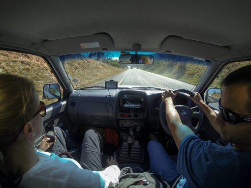 Foto de dentro do carro que mostra uma estrada asfaltada e pista simples.