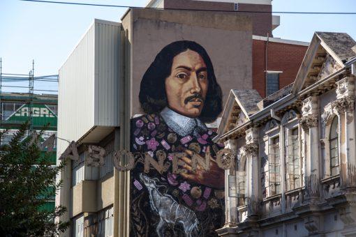 Grafite de um homem com roupas antigas e o letreiro Maboneng