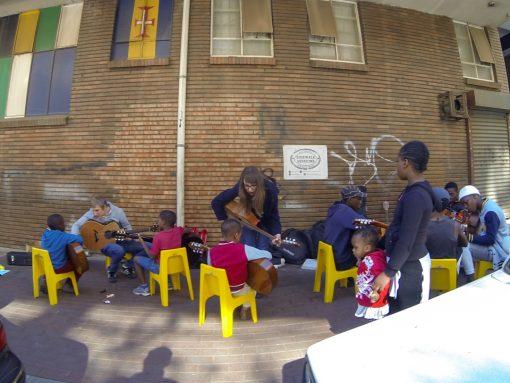 4 crianças tendo aulas de violão em uma calçada de Maboneng sentadas em cadeiras amarelas sob um fundo de tijolos aparentes.