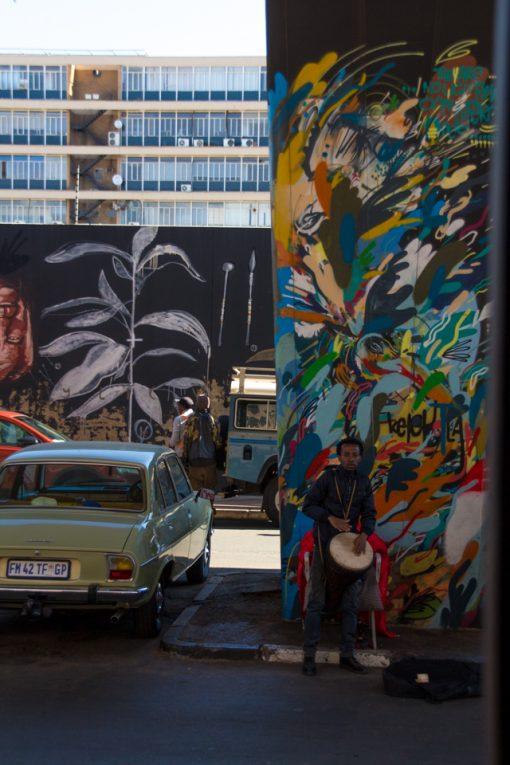 Homem tocando pandeiro embaixo de viaduto todo colorido por grafite.