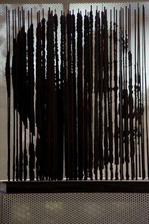 Vários filetes de ferro colocados sobre uma base revelam o rosto de Nelson Mandela.