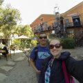 Selfie de Bruna e Diego na frente do Arts on Main, fábrica antiga de tijolos a vista onde hoje ocorre uma feira de comida e artesanato.