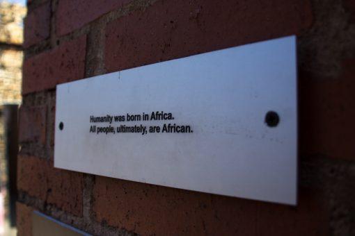 Frase no museu do apatheid que diz que a humanidade nasceu na África, logo todos somos africanos.