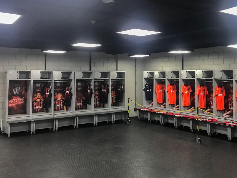 Armários no vestiário do atlético cada um com a foto do jogador e com as camisas, chuteiras e toalhas.