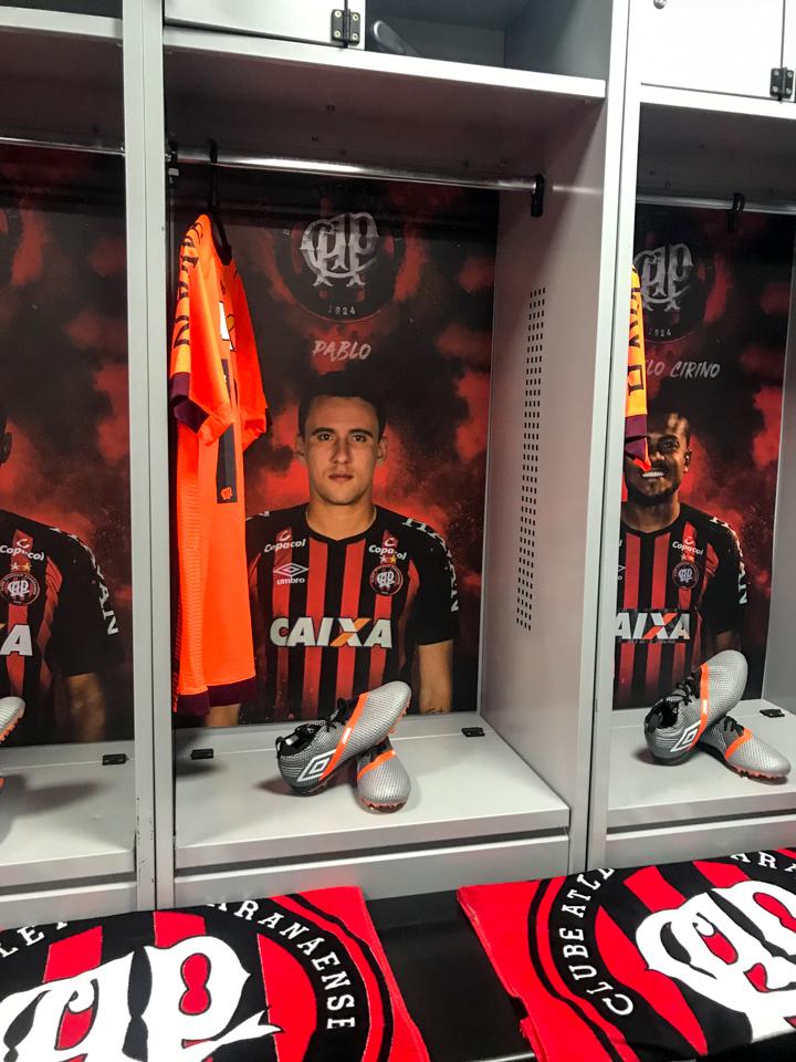 Camisa do jogador atleticano Pablo no seu armário do vestiário com a foto do jogador e ainda chuteira e toalha.