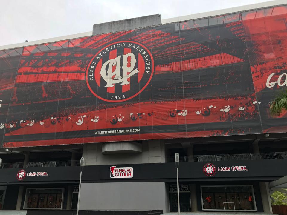 A entrada para a visita a Arena da Baixada tem uma fachada com o símbolo do Atlético e as cores vermelho e preto. A uma placa indicando furacao tour