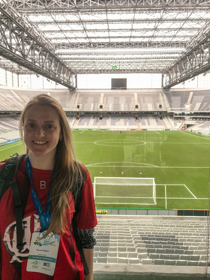 Visita a Arena da Baixada -Eu na arquibancada inferior do estádio com o campo ao fundo atrás da trave do goleiro. Pode-se ver o telão no final e uma bandeira do Brasil pendurada.