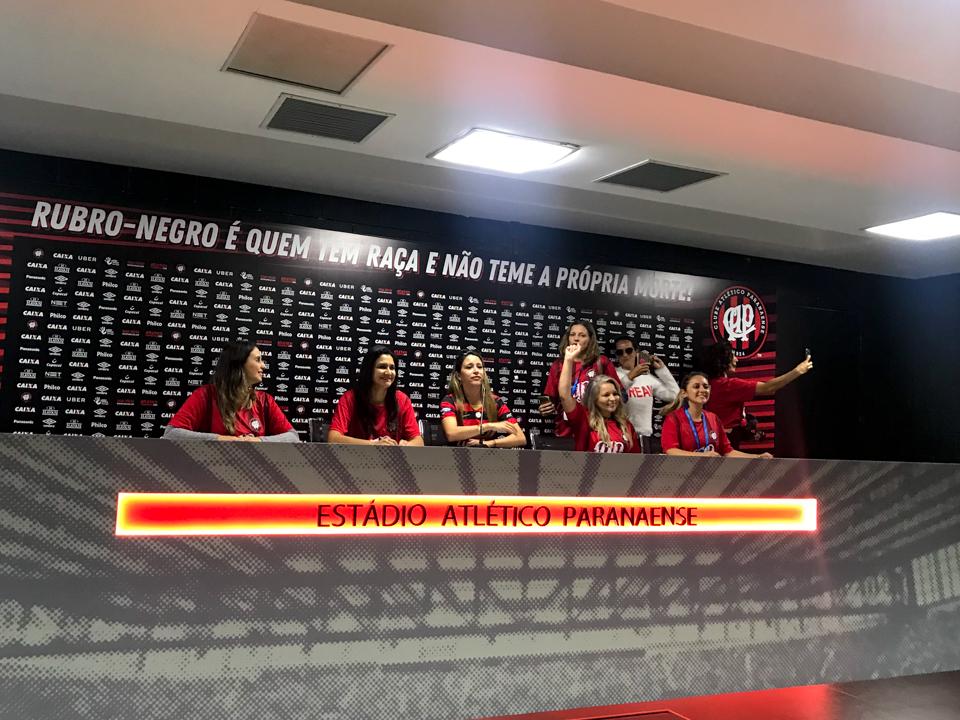 Sala de imprensa dos times visitantes do Atlético paranaense com apenas mulheres sentadas na bancada fingindo uma entrevista pós jogo