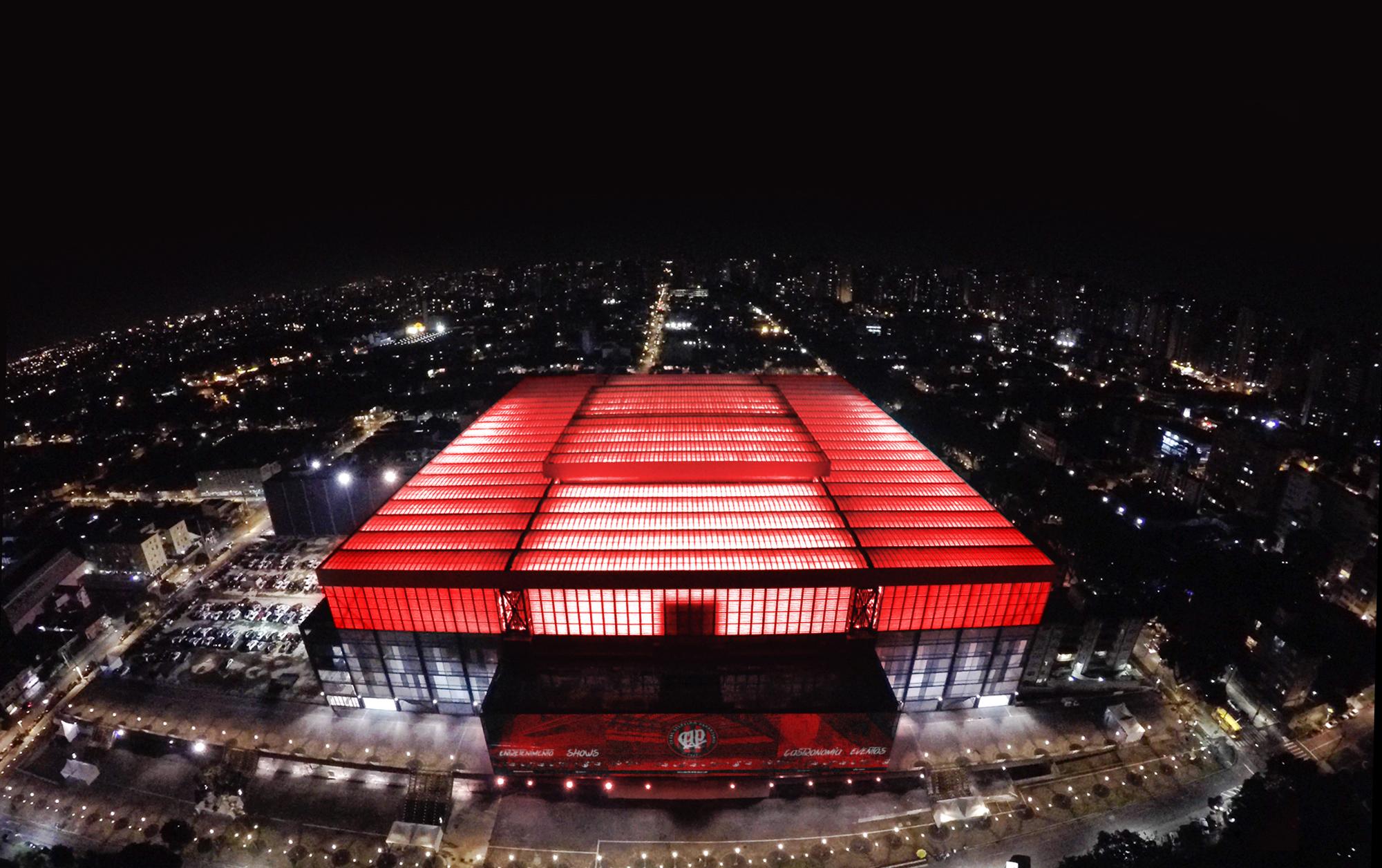 Vista área noturna da Arena com o teto todo iluminado de vermelho. Arena da Baixada Visitação