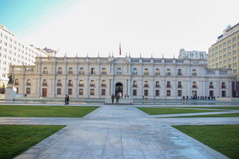 parte de trás do palacio la moneda onde há um grande gramado e um espelho d'água.