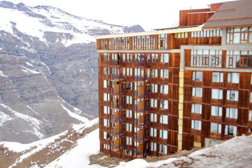 hotel do valle nevado com paredes que imitam madeira e montanha nevada ao fundo