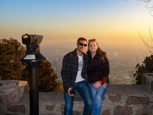 Eu e Diego sentados na mureta do Cerro san cristobal com Santiago ao fundo cheia de neblina