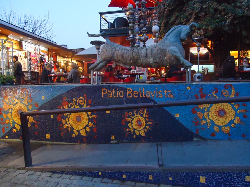 Mosaico em tons de azul e com flores amarelas do patio Bellavista com uma escultura de um cavalo sem patas