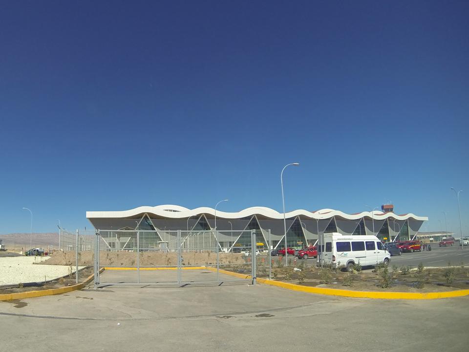 Pequeno aeroporto de Calama com algumas vans no estacionamento.