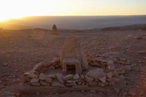 CAsinha construída de pedra com uma entrada e várias pedras ao redor formando um pequeno muro e pôr do sol ao fundo