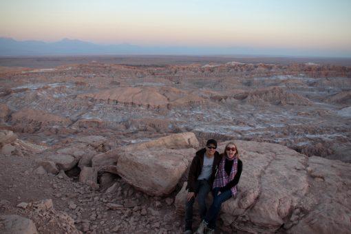 Entardecer no valle de la muerte, eu e Diego sentados em uma pedra e vendo ao fundo um vale cheio de sal incrustado na rocha.