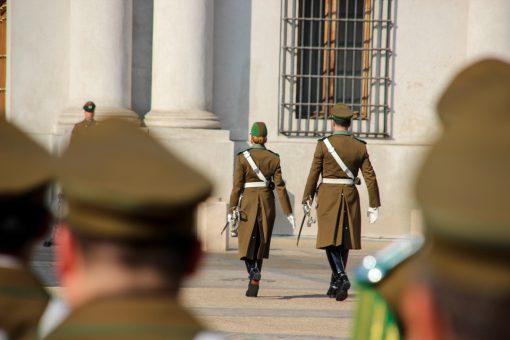 Soldados marchando para entrar no palácio. Um homem e uma mulher.