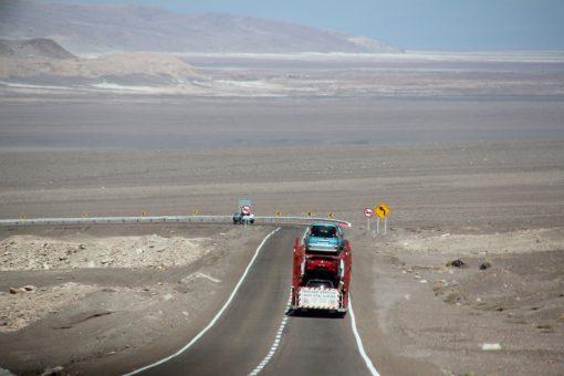 Estada de Calama até San Pedro de Atacama. Um carro pequeno e um caminhão cegonha a nossa frente.