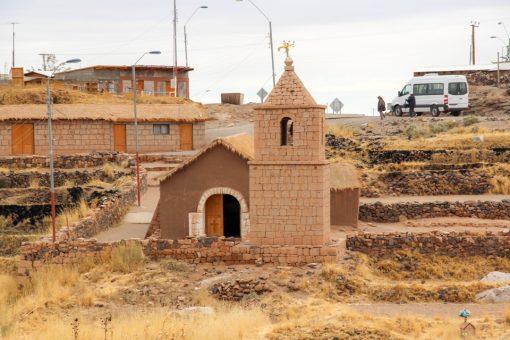 Igreja de socaire vista de fora. As paredes são cor de terra e o telhado é de palha