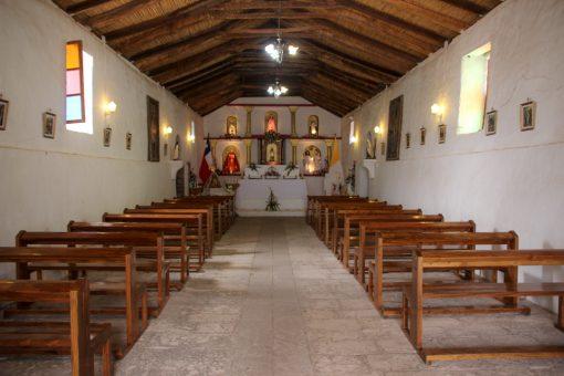 Interior da igreja de toconao com bancos dos dois lados, paredes brancas e teto de palha. O altar tem seis imagens de santos.