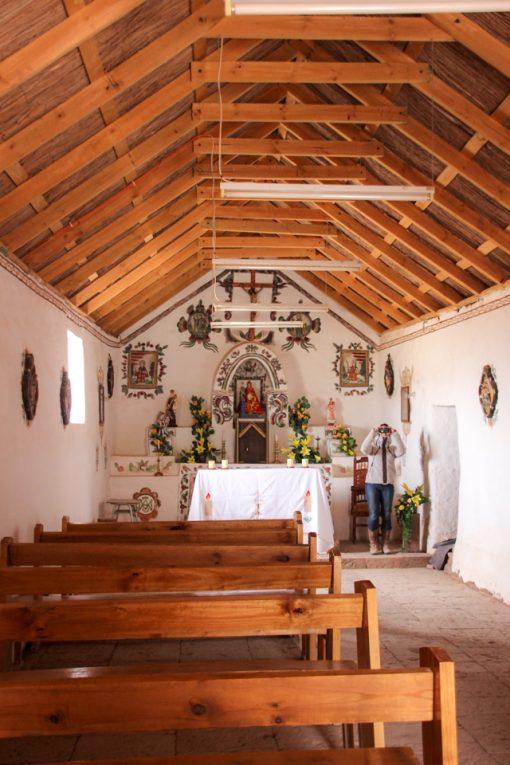 Interior da igreja de socaire com bancos apenas do lado esquerdo. as paredes são brancas e o teto é de madeira. O altar é simples com algumas flores e estátuas de santos.
