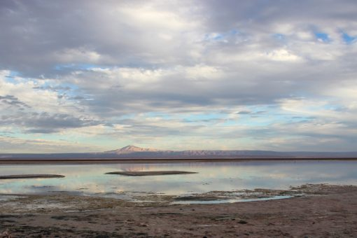 LAguna Chaxa refletindo um vulcão ao fundo e as nuvens do céu azul