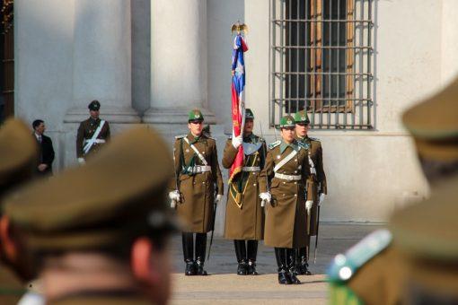 Grupo de quatro soldados mulheres empunhando espadas e uma delas segurando a bandeira do Chile.