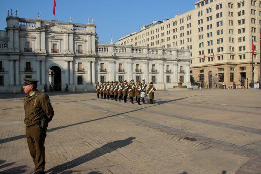 Duas filas de soldados com um tocando tambor a frente chegando no palacio de La moneda