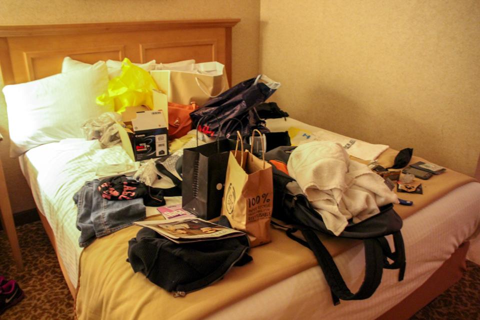 Cama de casal de hotel em Las Vegas cheia de sacolas de compra, caixas, mochila e toalha de banho