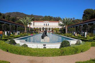 Museus getty - Entrada do Getty Villa com um enorme espelho d'água rodeado de caminhos cobertos e algumas palmeiras