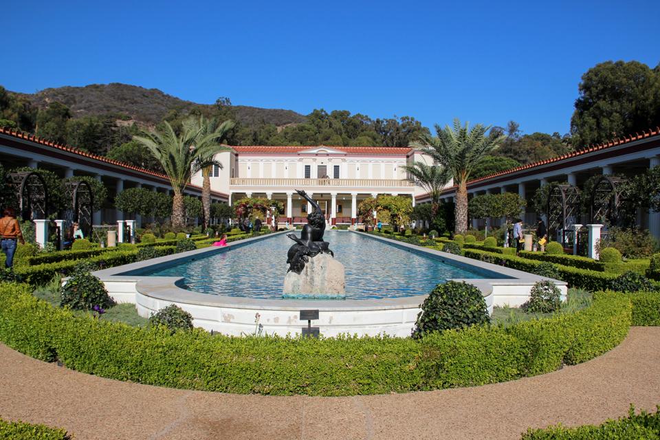 Entrada do Getty Villa com um enorme espelho d'água rodeado de caminhos cobertos e algumas palmeiras