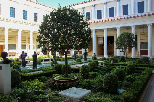 Jardim de inverno na parte do átrio com diversos arbustos, duas árvores baixas e diversas estátuas