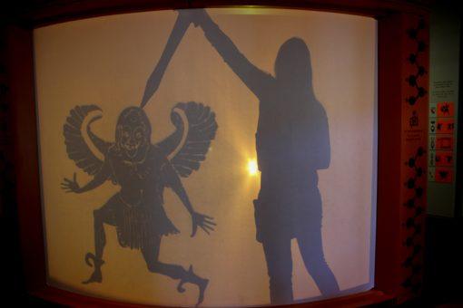 Sla interativa do Getty Villa onde é possível brincar com a sombra. Na foto estou com uma espada derrotando um deus alado e mascarado