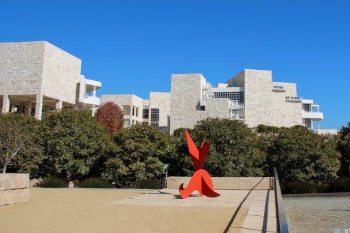 Escultura moderna na cor vermelha na parte exterior do Getty com árvores e o prédio ao fundo.