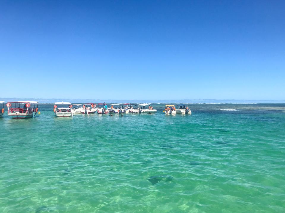 Diversas lanchas estacionadas nas galés de maragogi num mar de verde clarinho