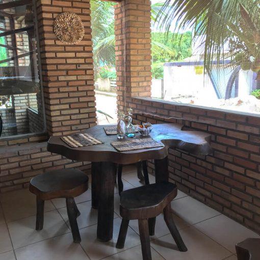 Mesa na parte exterior do restaurante onde era servido o café da manhã. A mesa é feita com um enorme tronco de árvore