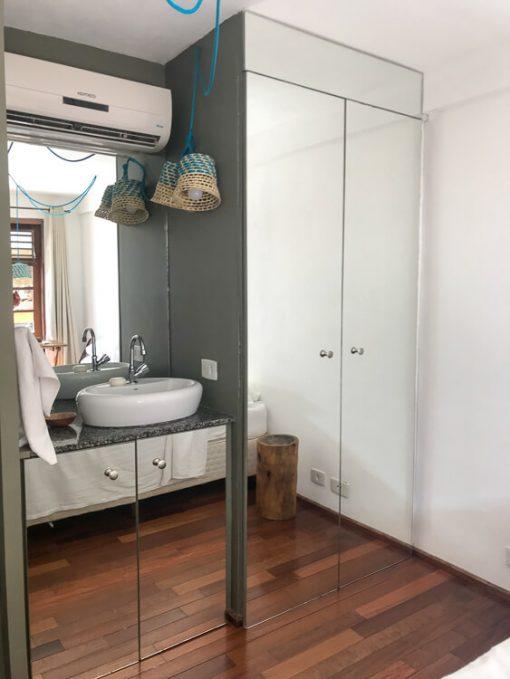 A pia fica fora do banheiro, no quarto. Fica ao lado do guarda roupa com tudo revestido de espelhos.