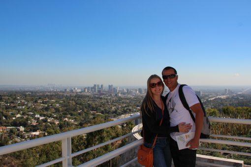 Vista da cidade de Los Angeles a partir do Getty Center com um céu azul e eu e o Diego posando pra foto.