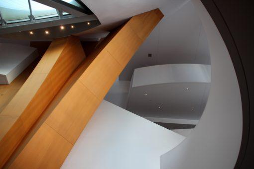 As formas diferentes continuam na parte de dentro, mistura de de formas brancas, vidro e madeira