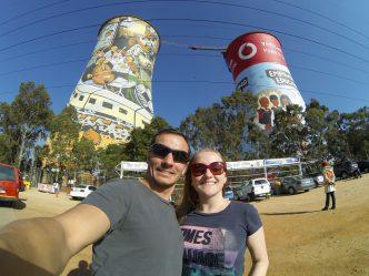 Diego e Bruna na frente das Orlando Towers que estão pintadas com cenas do cotidiano de Soweto.