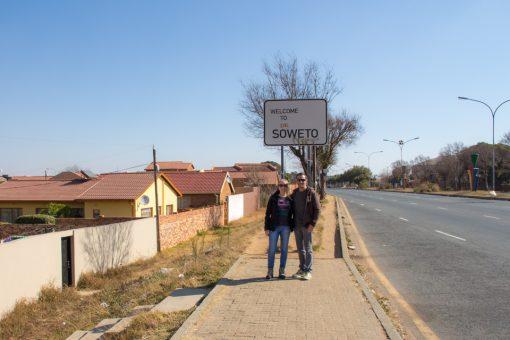 Eu e Diego posando em frente a placa escrito Welcome to soweto com vuvuzelas no canteiro da rua.